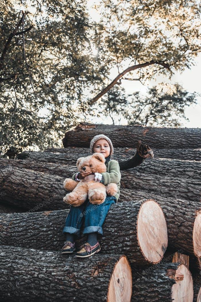 Little girl with a teddy bear sitting on logs