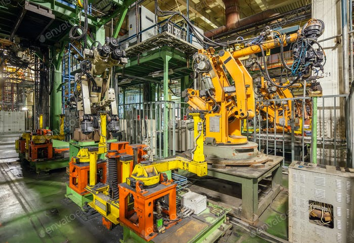 Bankrupt and abandoned automobile plant. Yellow robots welding cars in a production line.