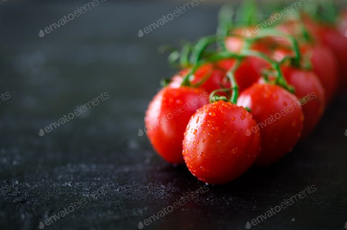 Fresh cherry tomatoes on black background with basil, spices. Copy space