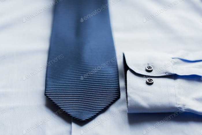 close up of shirt and blue patterned tie
