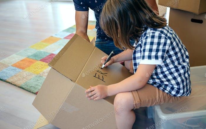 Junge schreibt in einem Umzugskarton