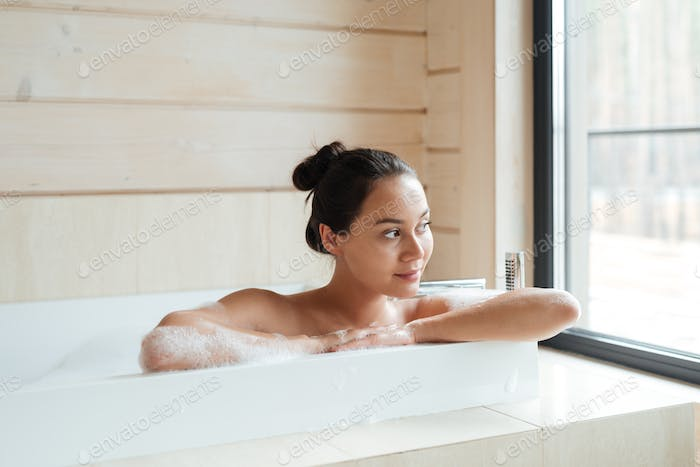 Smiling woman sitting and looking at the window in bathtub