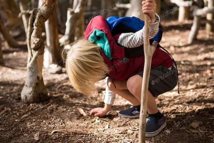 Kleines Mädchen mit Stock berühren Boden