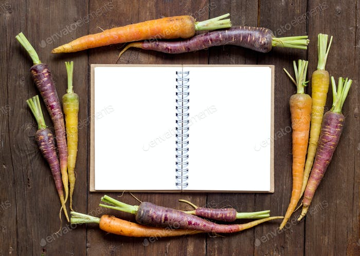 Fresh organic rainbow carrots with Recipes book