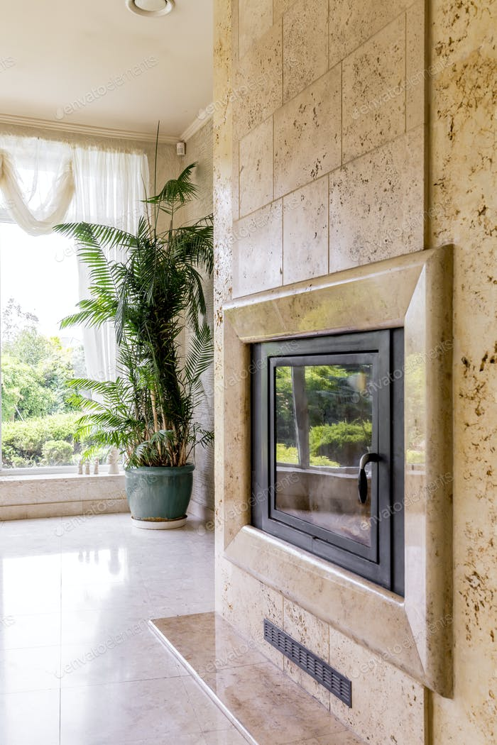 Travertine fireplace next to big window