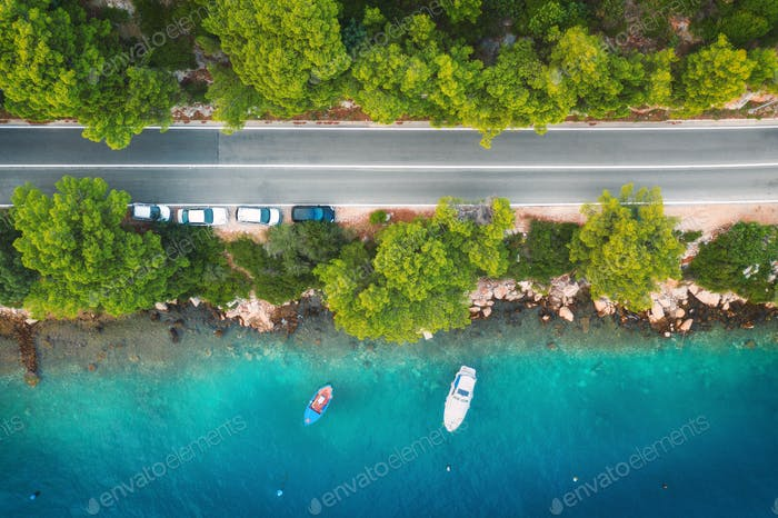 Aerial view of road in beautiful green forest and boats and yacht
