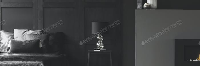 Real photo of an elegant lamp with a glass base on a simple nigh