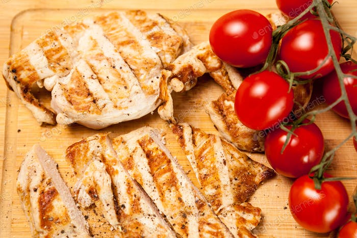 Fresh grilled chicken breast on wooden board next to tomatoes
