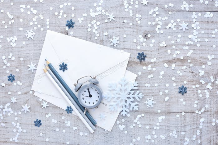 Alarm clock, pencils and envelopes for congratulations, snowflak