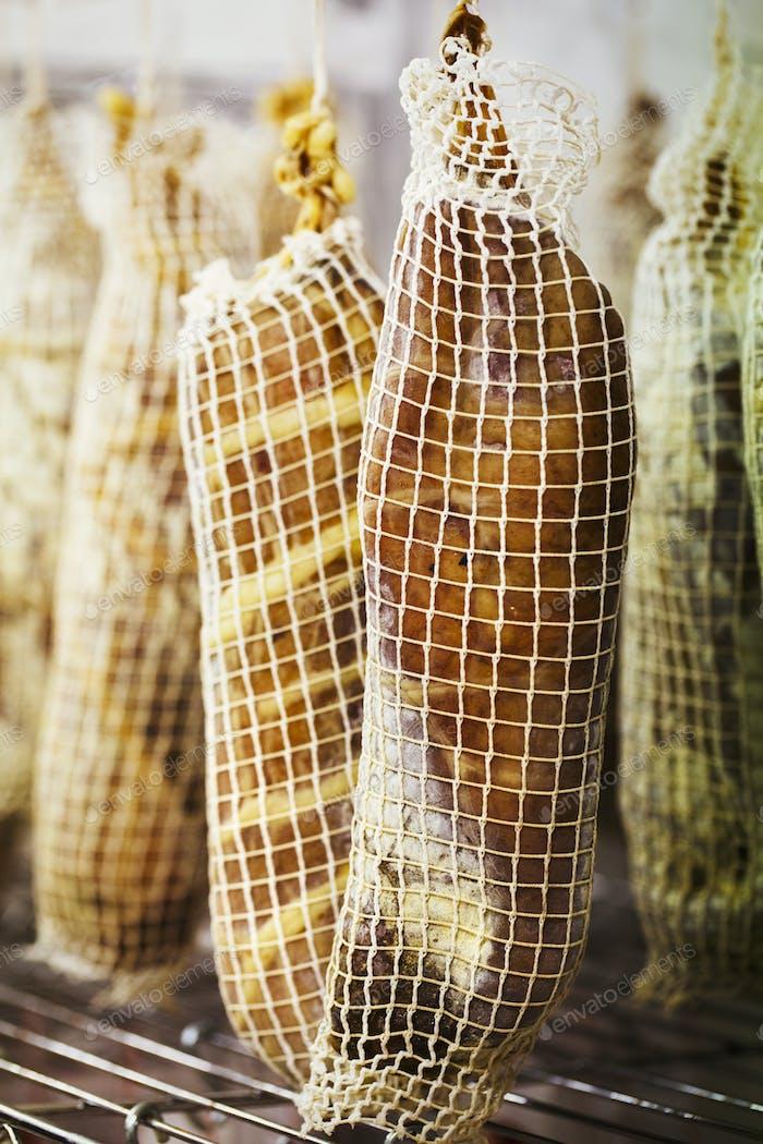 Nahaufnahme von luftgetrocknetem Fleisch in Netze eingewickelt, in einer Wurstwaren hängen.