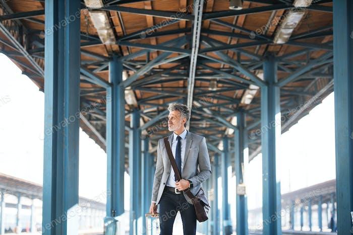 Reife Geschäftsmann auf einem Bahnhof.
