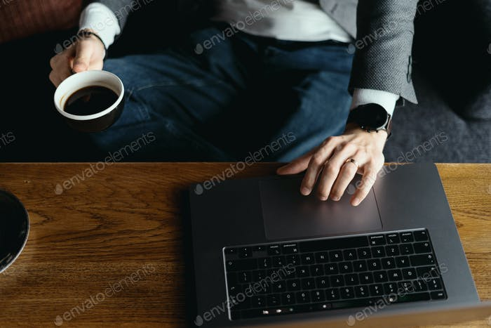 Business man hands working on laptop holding cup of coffee