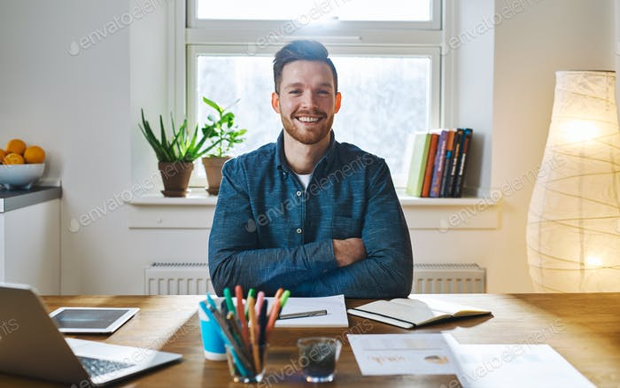Bearded man at desk with folded arms