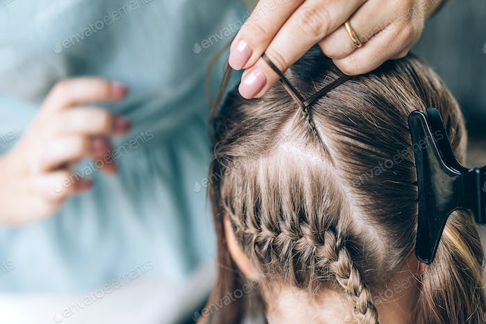 Mother does hair braid to her daughter, close up photo