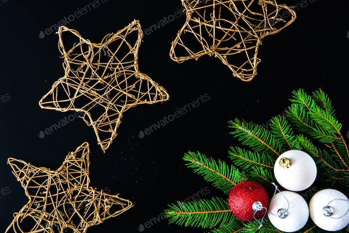 Christmas background with balls, golden snowflakes and fir tree branches on black