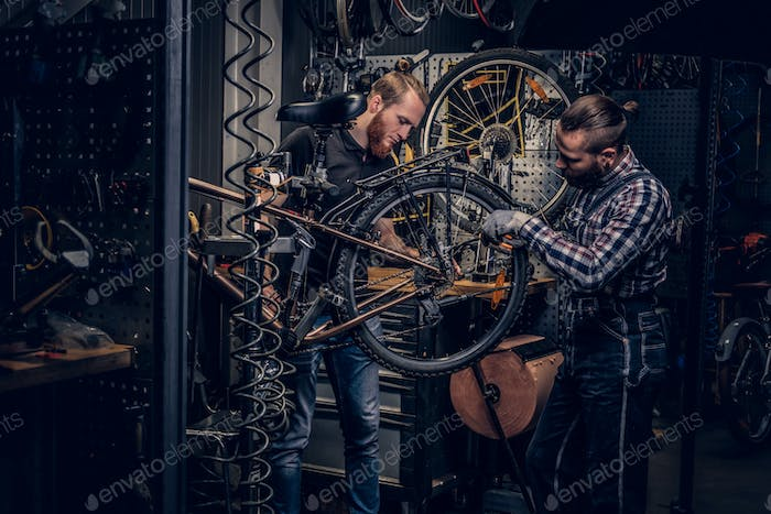 Bicycle mechanic in a workshop with bike parts and wheel on a background.