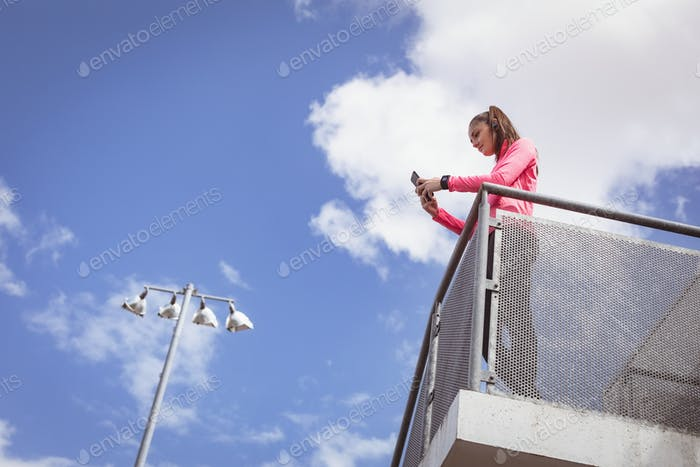 Woman using mobile phone in the balcony of stadium