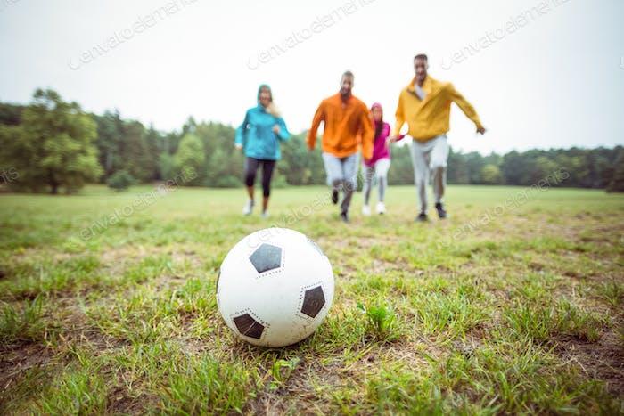 Freunde laufen in Richtung Fußball auf dem Land