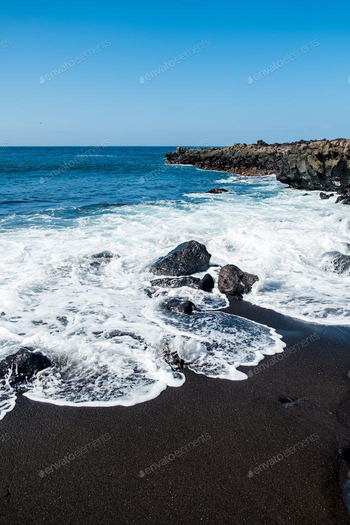 hermosa vista sobre el agua del océano y la Arena de lava negra