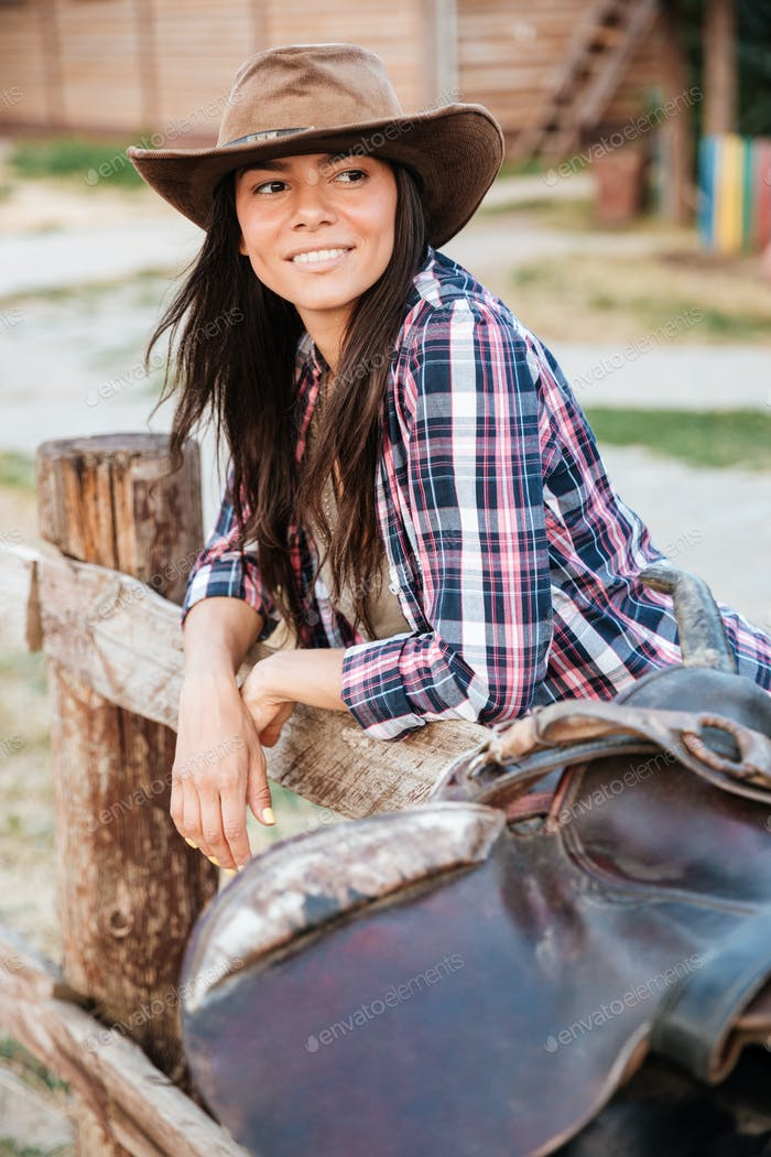 Woman cowgirl leaning on fence in village and looking away