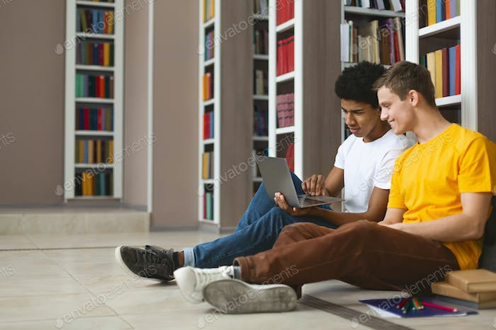 Two teenage guys studying on floor at college library