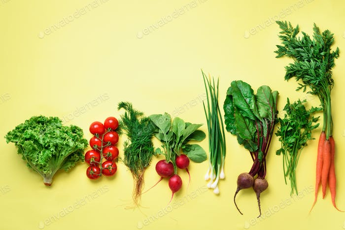 Organic vegetables on yellow background with copy space. Top view of carrot, beet, pepper, radish