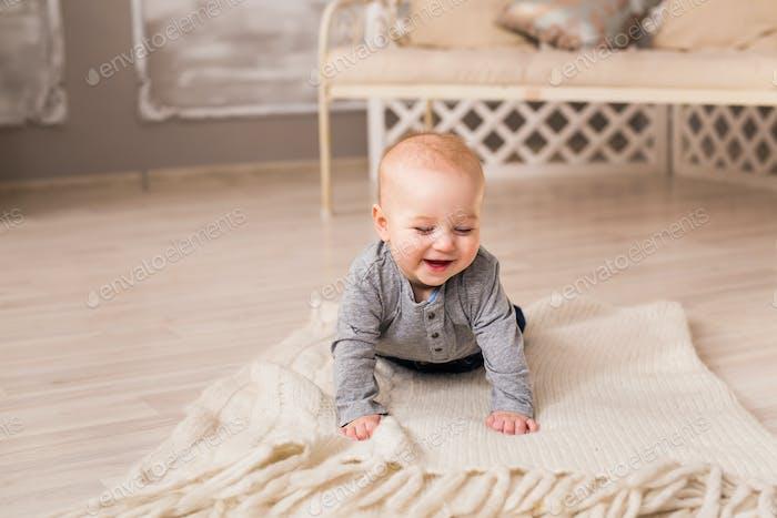 Lachende Baby Junge liegend auf Bauch zu Hause