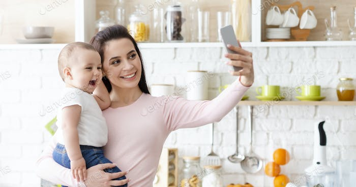 Happy mother with baby photographing themselves on cellphone