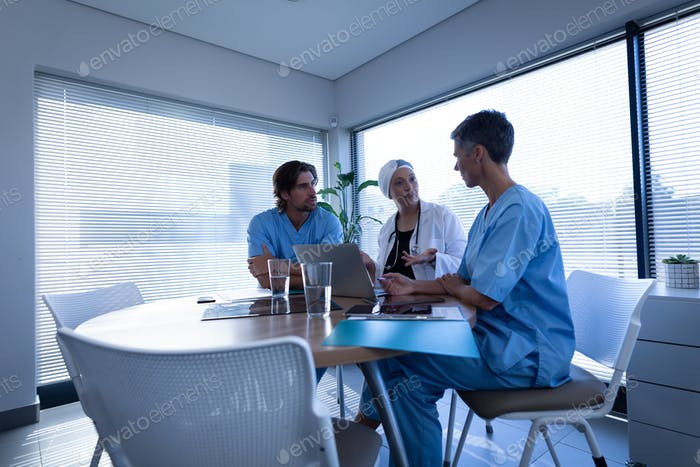 Side view of multi ethnic doctors discussing over laptop in clinic at hospital