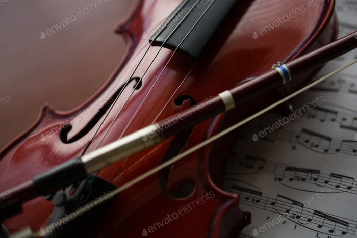 Close up of brown violin with sheet music