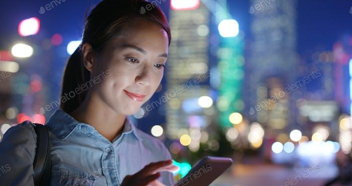 Frau Blick auf Handy in der Stadt in der Nacht