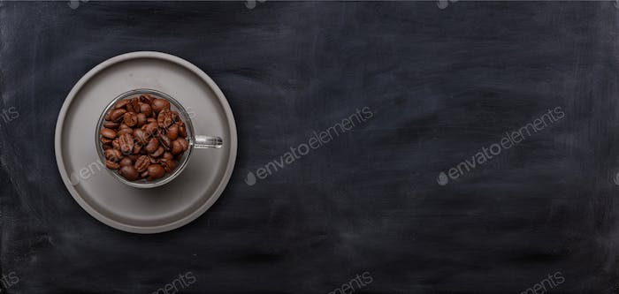Coffee cup and beans on black chalkboard background, banner