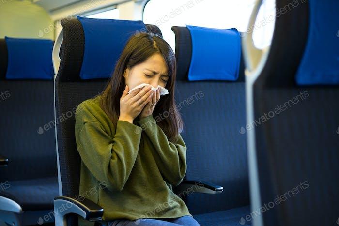 Mujer estornuda en el compartimento del tren