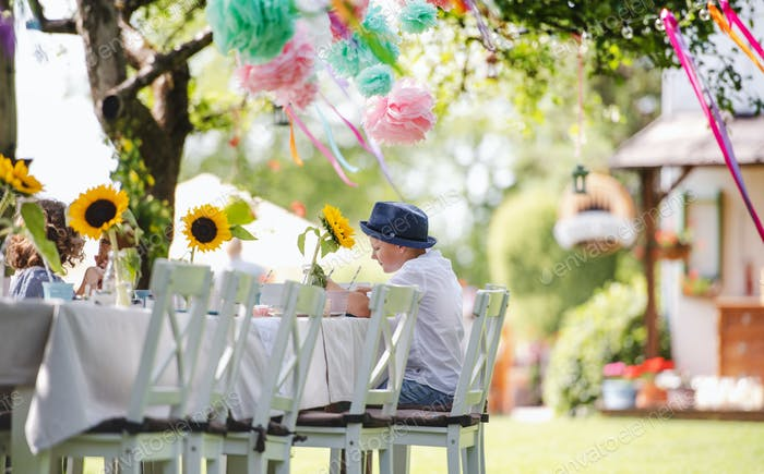 Small boy sitting at the table outdoors on garden party in summer, eating