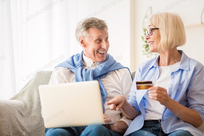 Happy mature couple making online purchases on laptop