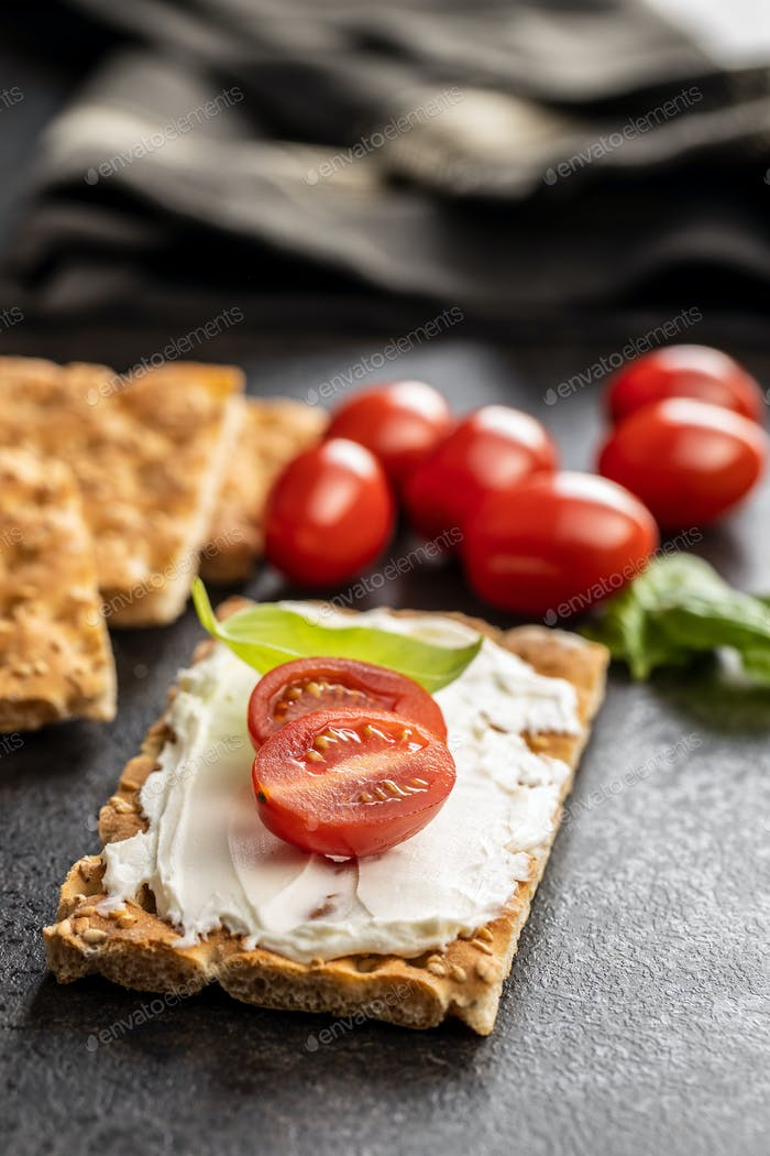 Diät Knackebrot. Knäckebrot mit cremigem Käse., Kirschtomate und Basilikumblatt.