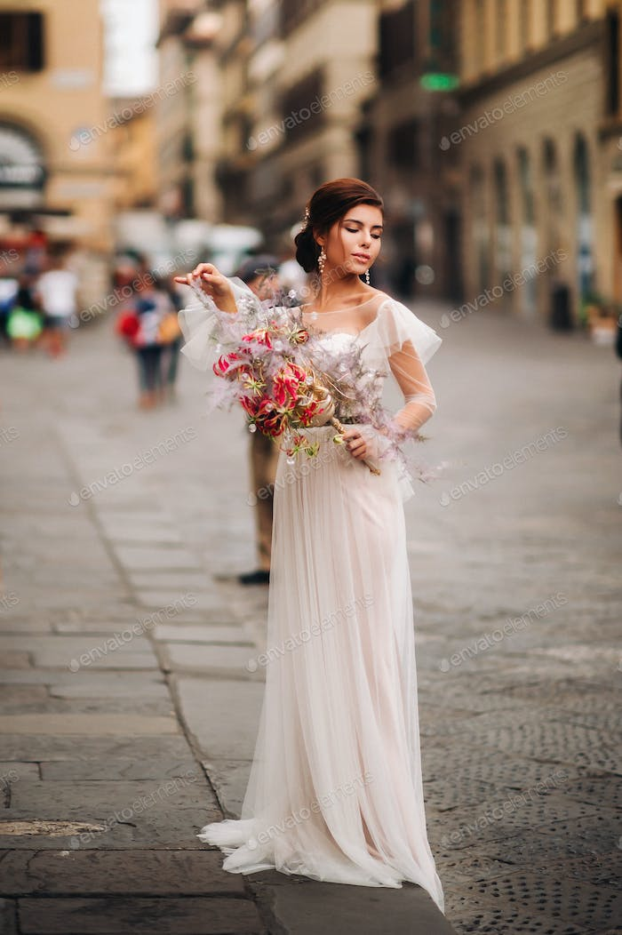 the girl-bride is with beautiful flower pattern as a mask in Florence, stylish bride in a wedding