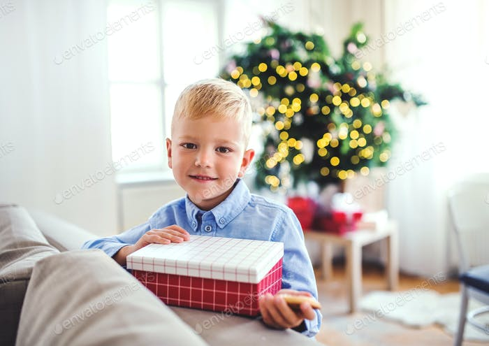 A small boy with a present at home at Christmas time.