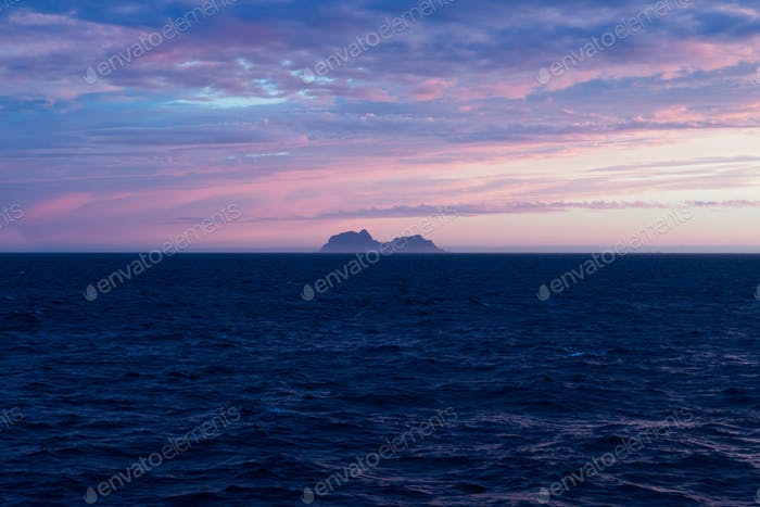 Lonely island of the coast of Lofoten by sunset