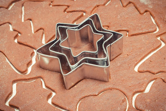 Dough for Christmas cookies with cookie cutters in shape of star