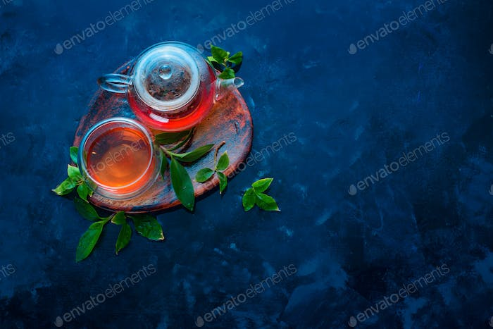 Teapot and double wall glass with tea leaves on a wooden coaster. Dark blue background flat lay with