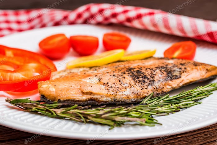 Salmon steak with vegetables close up