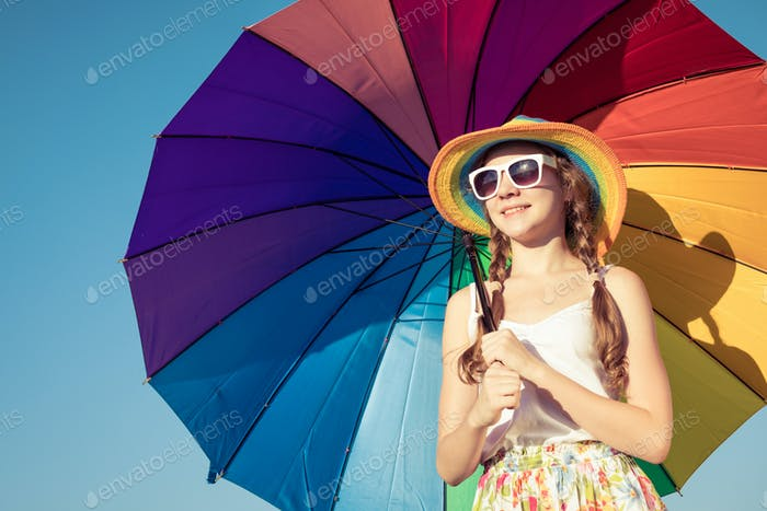 teen girl with umbrella standing on the beach at the day time.