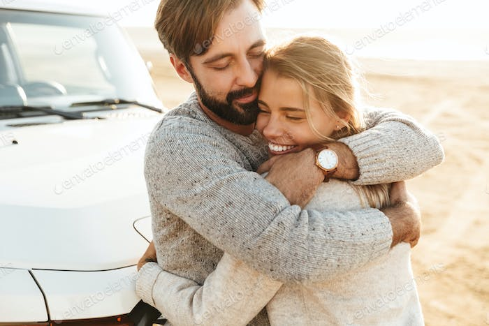 Happy young couple in love embracing while leaning on a car