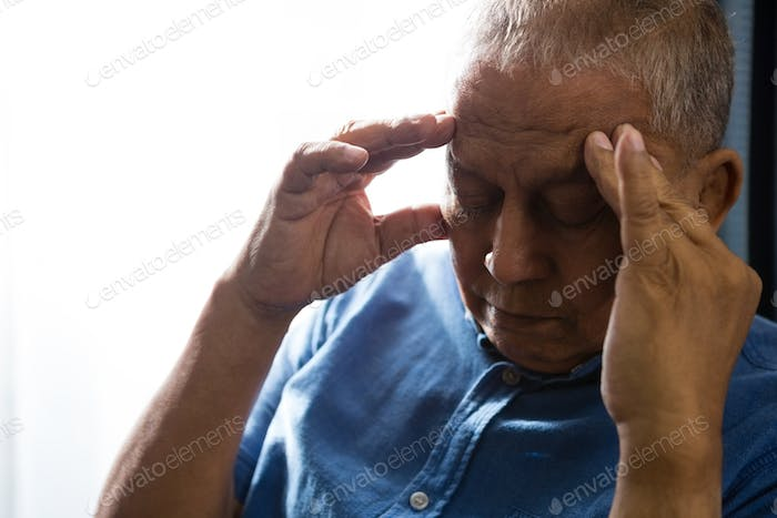 Close up of senior man pressing head while sitting by window
