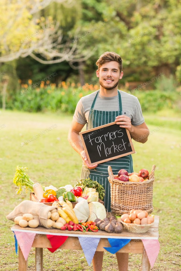 Handsome farmer standing at his stall and holding chalkboard on a sunny day