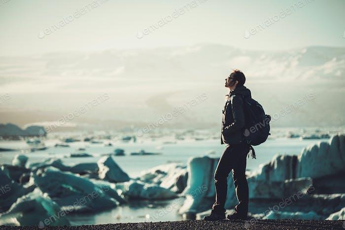 Woman explorer lookig at Jokulsarlon lagoon, Iceland.