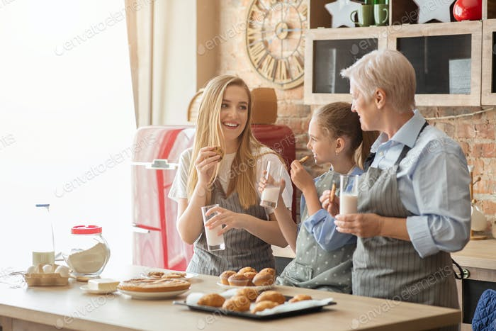 Beautiful family eating pastry with milk at kitchen