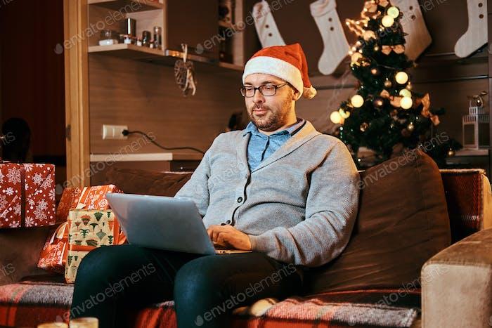 Glücklicher Mann in Brille halten Laptop und Blick auf die Kamera, während auf dem Sofa zu Weihnachten sitzen.