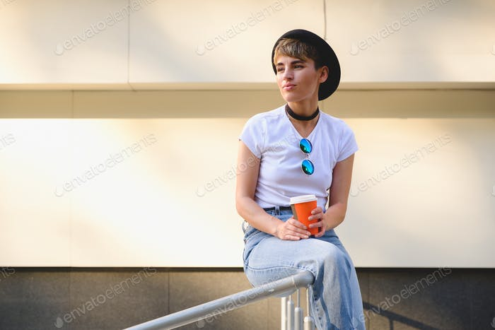 Portrait of female hipster with natural makeup and short haircut enjoying leisure time outdoors